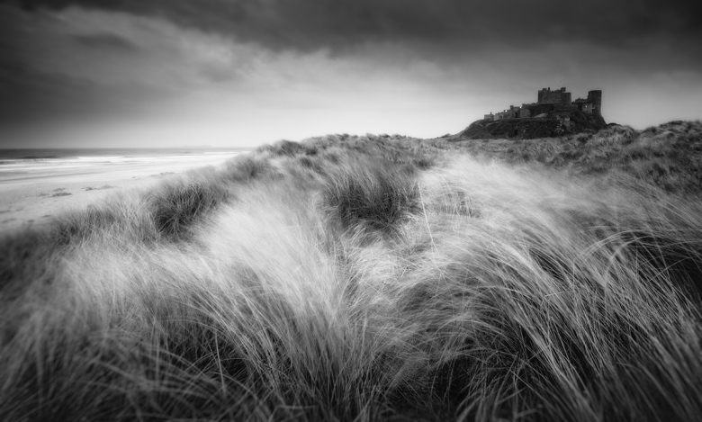 Bamburgh at sunset through the dunes